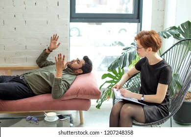 young man is lying on couch at female psychologist office and talking while doctor is making notes