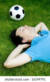 Young man lying on the grass with soccer ball