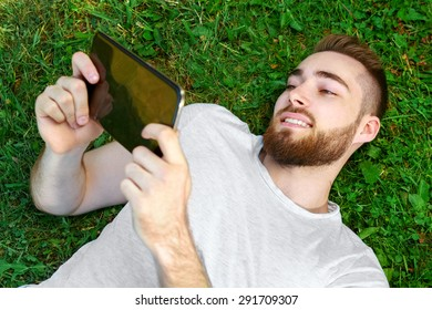 Young man lying on the grass in park with tablet.