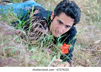 young man, lying on the grass looking at flower