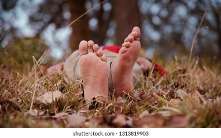 Young man lying on a ground with bare feet isolated unique photo