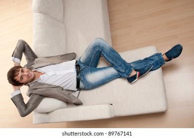 Young man lying on a sofa.
