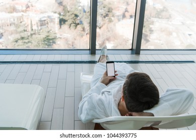 Young man lying on sunbed near pool with phone indoors. Luxury hotel with a great city view behind the window