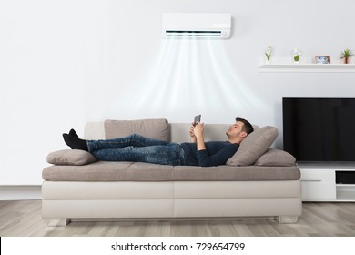 Young Man Lying Under Air Conditioner On Couch Using Tablet At Home