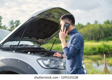 Young man make a phone call during car broken. Man need help.