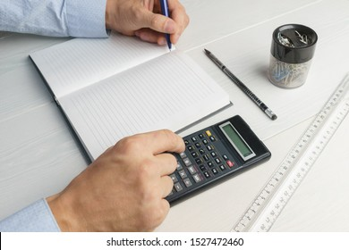 The young man makes calculations on a calculator and writes in a notebook