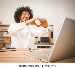 Young man makes video call, communicates via video link with friends. Arabic guy shows a heart sign with his hands expressing love and sympathy to his interlocutor. Toned image.