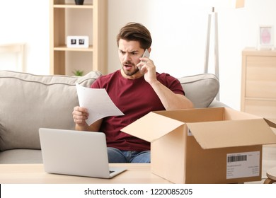 Young man making call about delivered parcel at home