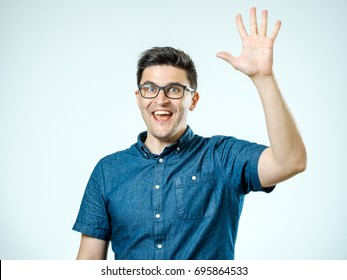Young man making high five gesture isolated on gray background