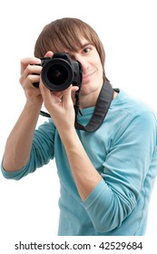 Young man making photo with professional camera. Over white