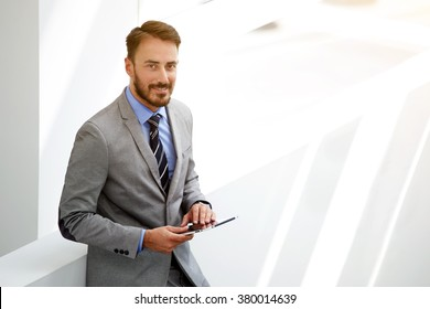 Young man manager in good mood holding touch pad while standing in hallway company near copy space area, smiling male prosperous and successful banker with digital tablet in hands look at the camera