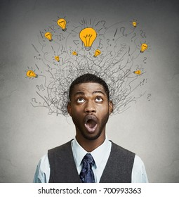 Young man with many idea light bulbs above head looking up isolated on gray wall background.
