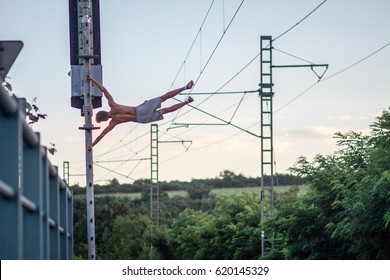 Young man Martin Sobol performs human flag calisthenic exercise in railway in height. Urban streetworkout photography.