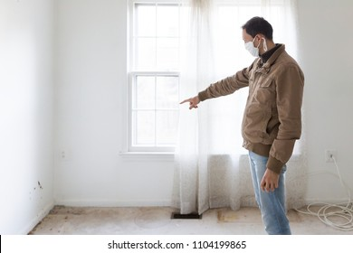 Young man in mask standing pointing at room wall carpet floor flooring, white painted walls, during remodeling renovation, cleaning, inspection of dirty mold, dust, trash in corner
