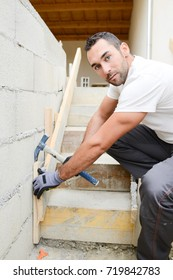 young man mason de-molding concrete stairs with hammer in a new house construction site