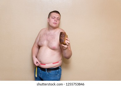 A young man measures his fat belly with a meter and holds bread in one hand