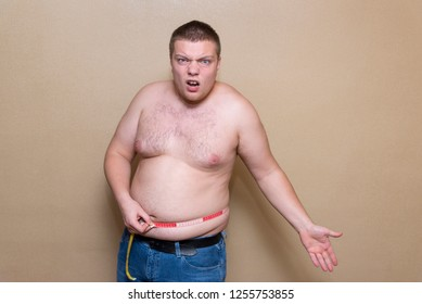 A young man measures his fat belly with a meter