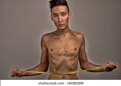 Young man measuring himself. Skinny young man posing fashion with a centimeter, anorexic look