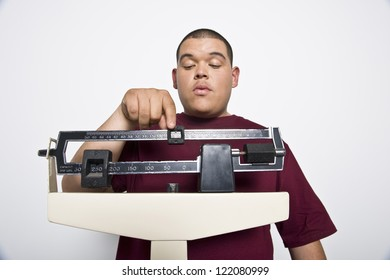 Young man measuring his weight on weighing scale in clinic