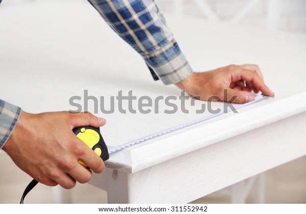 Young man measuring home furniture with measure tape, close up
