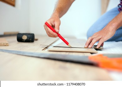 Young man measuring and marking laminate floor tile for cutting, installing laminate flooring. Close-up photo with focus on his hands. Home improvement and renovation concept