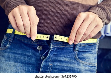 a young man with a measuring tape as a belt tries to fasten his trousers, because of the weight gain