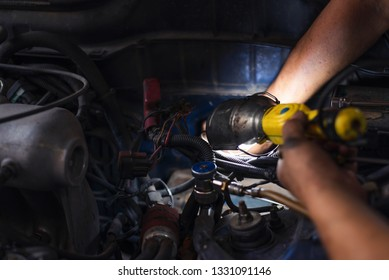 Young man mechanic repairing car in garage shop,car service, repair, maintenance and people concept - auto mechanic man with lamp working at car service center.