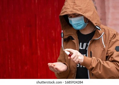 Young man in medical face mask is spraying a hand sanitizer on his hands. Using antibacterial gel for hands on the street during coronavirus pandemic. COVID-19 quarantine situation in center of Europe