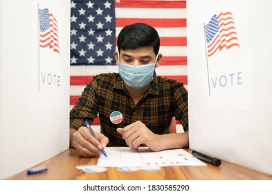 Young man in medical mask busy inside the polling booth with US flag as background - Concept of in person voting with covid-19 safety measure at US election