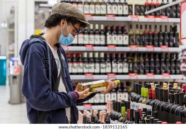 A young man in a medical mask chooses wine in a supermarket. Coronavirus pandemic.