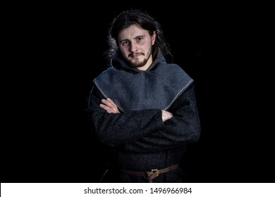 a young man in medieval clothes crossed his arms, half-lenght portrait. living history, historical reconstruction of clothing  of the 9-11th century, the Viking era, Scandinavia