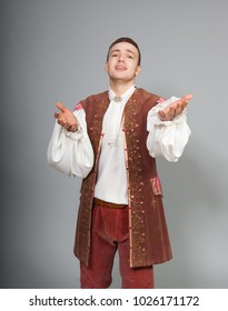 A young man in a medieval costume of a French nobleman on a gray background in the studio