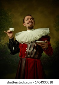 Young man as a medieval knight on dark studio background. Portrait in low key of male model in retro costume. Drinking morning coffee. Human emotions, comparison of eras and facial expressions concept