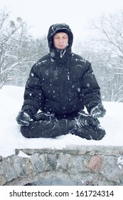 A young man meditates in the lotus position on the snow