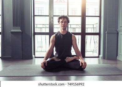 Young man meditates while practicing yoga in lotus pose. Freedom calmness and relax concept