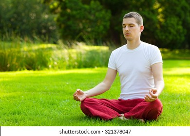 Young man meditating in half lotus - beautiful park as a background.