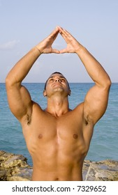 Young Man Meditating Near Ocean with Hand up in the Air