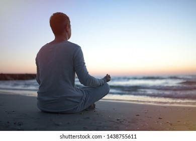 young man in meditation near the sea. Concept of pray. Adult practice yoga on the beach at sunset.