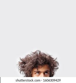 Young man with messy long hair looking up, saw half face, isoalted white background.