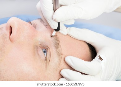 Young man microblading procedure to improve the condition of a mans eyebrows in a beauty salon.