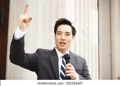 A young man with a microphone and his finger in the air giving a speech.
