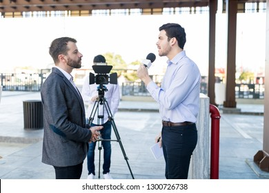 Young man with a microphone interviews a well-dressed celebrity outdoors