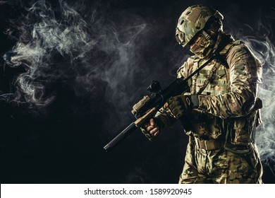 young man from military forces in green military wear try to shoot on rifle gun through smoke fogger