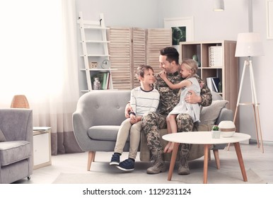Young man in military uniform with his children on sofa at home