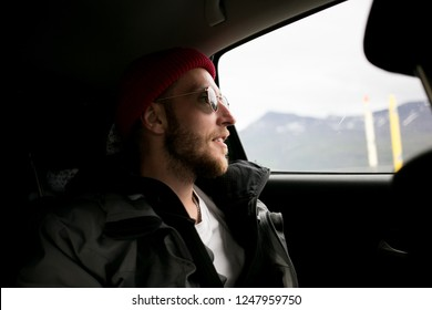 Young man in millennial or hipster outfit, jacket and red beanie sits in backseat of passenger car, looks out of window at scenery passing by during roadtrip adventure. Moody cinematic shot