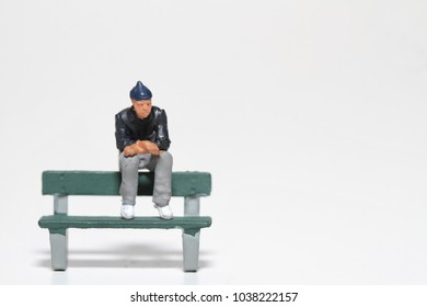 young man in miniature sitting lonely on a bench