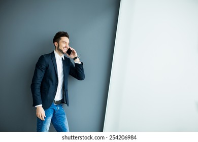 Young man with mobile phone by the grey wall