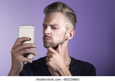 Young man with mobile phone having doubts