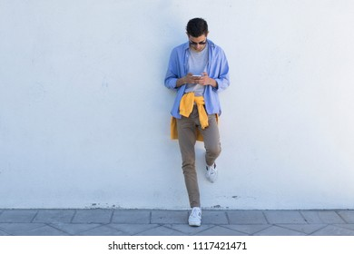 young man with mobile phone on the wall
