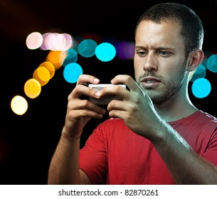 young man with mobile phone at shopping center by night